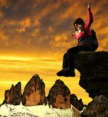 Girl sitting on a rock, in the background Tre Cime di Lavaredo at sunset ,Dolomite Alps, Italy