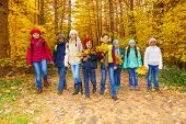 Kids group with maple leaves bunches walk together
