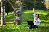 foto of independent woman  - Excited mature woman winning holding fist up high screaming of happiness with laptop - JPG