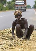 Old Dark-skinned Farmer Works His Mellet On Public Road.