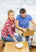 repair, moving in and people concept - smiling couple opening , unpacking cardboard box with dishes at home