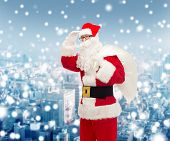 christmas, holidays and people concept - man in costume of santa claus with bag looking far away over snowy city background