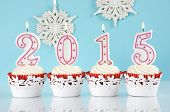 Happy New Year For 2015 Red Velvet Cupcakes In Red And White Theme With Lit Candles And And Snowflak