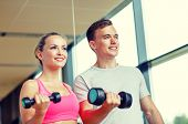 fitness, sport, exercising and diet concept - smiling young woman and personal trainer with dumbbells in gym