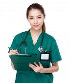 Asian Doctor write on clipboard