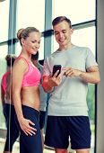 fitness, sport, exercising, technology and diet concept - smiling young woman and personal trainer with smartphone in gym