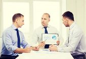 business and office concept - serious businessman showing others charts in office