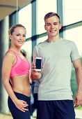 fitness, sport, advertising, technology and diet concept - smiling young woman and personal trainer with smartphone blank screen in gym