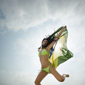 Young beautiful woman jumping with Brazil flag on beach