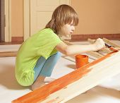 Boy With Blond Hair Painting A Board