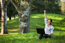stock photo of independent woman  - Excited mature woman winning holding fist up high screaming of happiness with laptop - JPG