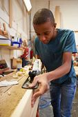 stock photo of carpentry  - Apprentice Planing Wood In Carpentry Workshop - JPG