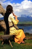 picture of flute  - A beautiful girl in a historical costume playing her flute in an open landscape with a lake - JPG