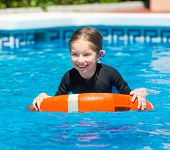 image of lifeline  - little girl swims in a wetsuit with a lifeline in the pool in  summer - JPG