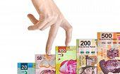pic of pesos  - Hand climbing a Mexican peso bill mountain - JPG