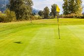 image of flag pole  - a golf hole with a flag pole in a beautiful golf course