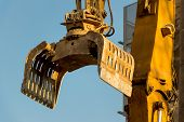 pic of dredge  - excavator on a construction site during the demolition of a hauses - JPG