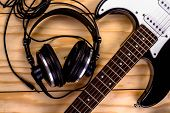 stock photo of sounding-rod  - electric guitar and a professional grade headphones on wooden table - JPG