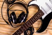 picture of sounding-rod  - electric guitar and a professional grade headphones on wooden table - JPG