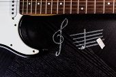 stock photo of sounding-rod  - black electric guitar and treble clef on dark table - JPG