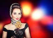 stock photo of lollipops  - Young beautiful woman in retro pin up style with lollipop on the bright background - JPG