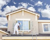 picture of residential home  - Busy House Painter Painting the Trim And Shutters of A Home - JPG