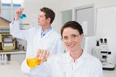 stock photo of beaker  - Scientists working attentively together with beakers in laboratory - JPG