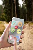 foto of dirt road  - Hand holding smartphone against narrow dirt road leading to two different track along trees - JPG