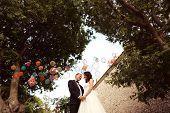 image of nea  - Happy bridal couple holding hands nea big wall - JPG