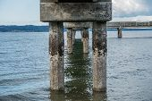 stock photo of tide  - Pier pilings encrusted with barnacles are revealed at low tide - JPG