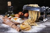 picture of food preparation tools equipment  - Metal pasta maker machine and ingredients for pasta on wooden background - JPG