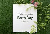 pic of recycled paper  - Earth Day April 22 Concept with recycled paper in grass with fern and butterfly and text - JPG