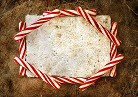 pic of candy cane border  - Christmas border with a red and white candie canes  around blank paper as a copy space on wooden planks - JPG