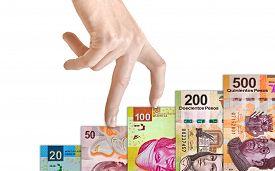 stock photo of pesos  - Hand climbing a Mexican peso bill mountain - JPG