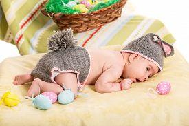 stock photo of bunny costume  - Newborn baby girl in crochet bunny costume with Easter eggs - JPG