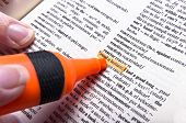 Woman's fingers and marker on dictionary