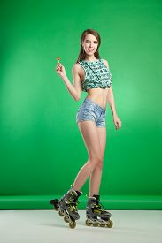 picture of lollipops  - Very attractive woman with lollipop in sexy outfit posing on green studio background wearing inline rollerskates - JPG