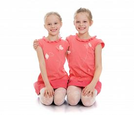 foto of identical twin girls  - two cute twin girls sitting on the floor and hug - JPG