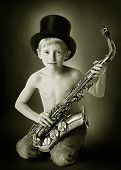 young boy with hat and sax in black white