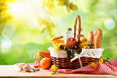 Picnic Wicker Basket With Food On Table In The Field poster