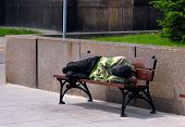 Homeless sleeping on bench during the day.