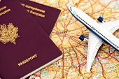 A model passenger airplane or jetliner, French passports on a road map of Paris, France.