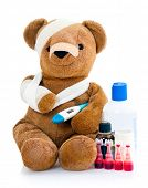 Sick teddy bear wrapped in bandages with underarm thermometer and bottles of medicinal drugs, isolat