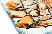Crepes with chocolate syrup drizzle and coconut shavings.