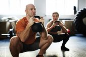 Young sporty woman and middle-aged bodybuilder doing kettlebell squat exercise during intensive trai poster