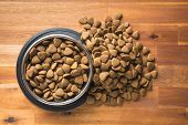 Dry kibble dog food in metal bowl on wooden table. Top view. poster