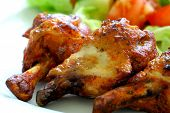 stock photo of chicken wings  - Grilled chicken on a white plate with vegetables on the background - JPG