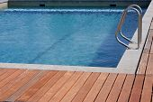 Luxury swimming pool blue water with a wooden deck