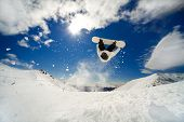 Snowboarder going off jump doing a backflip