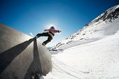 Snowboarder on wall ride with blue sky background